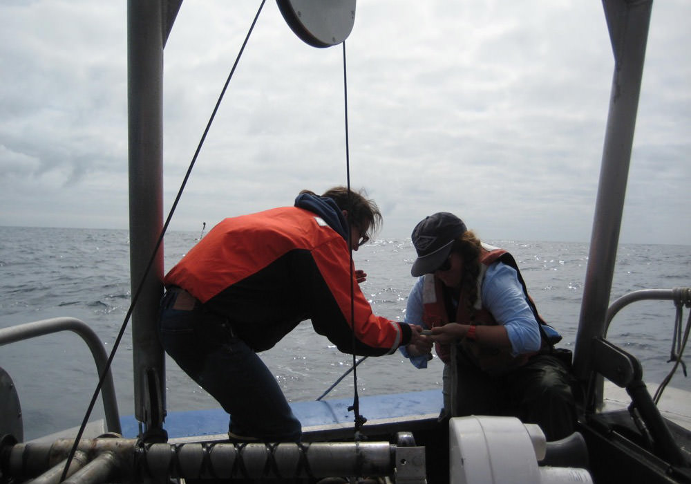 Danielle Lipski and Kate Hewett attach instruments to a mooring line as it is deployed