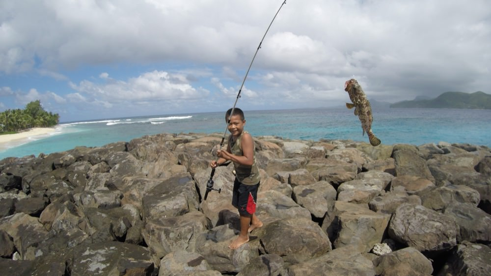 a boy holding a fishing pole with a fish