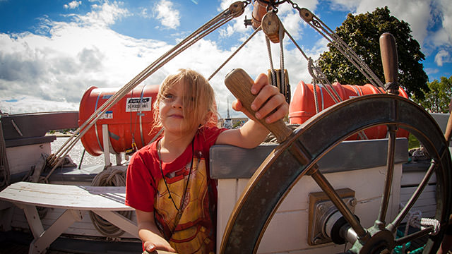 a girl at the steering wheel driving a boat
