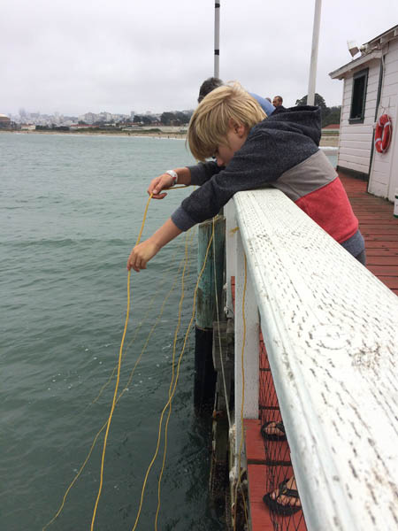 child dangles a string to catch a crab