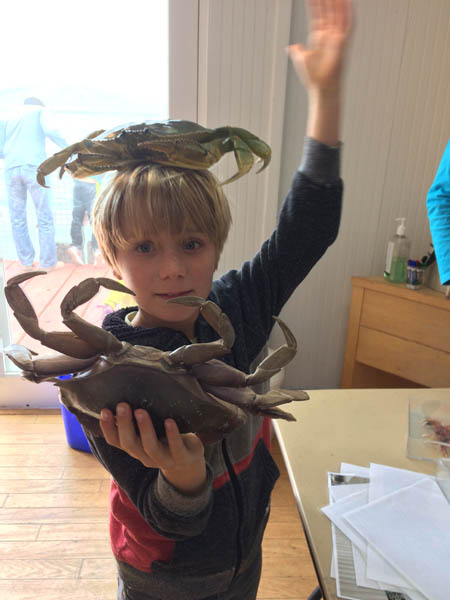 a child holds two large crabs