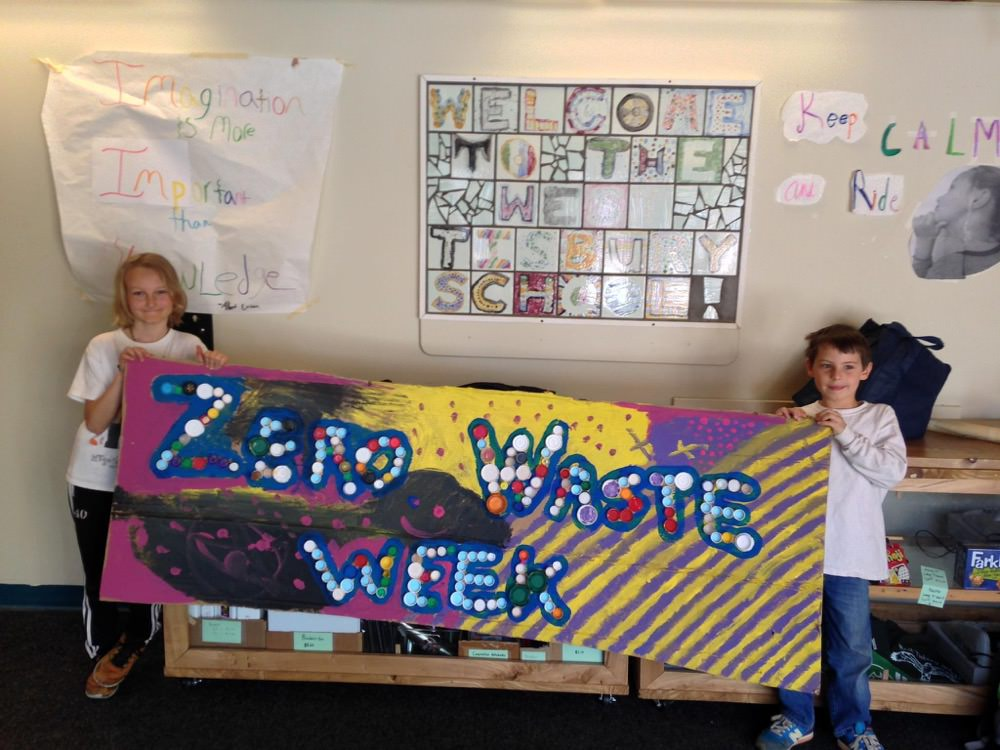 two students hold a zero waste week sign