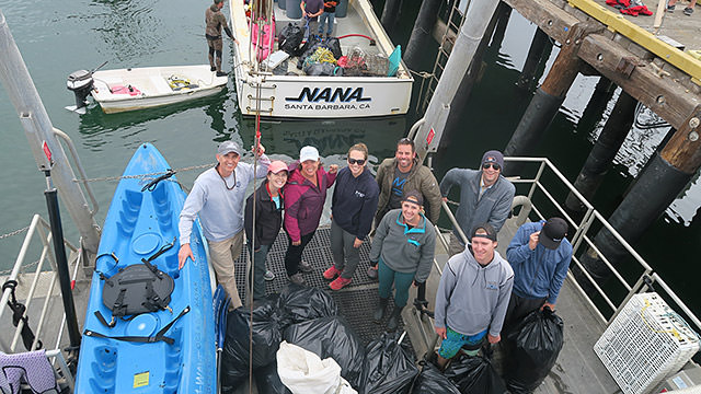 group of men and women standing with full trash bags in santa barbara harbor