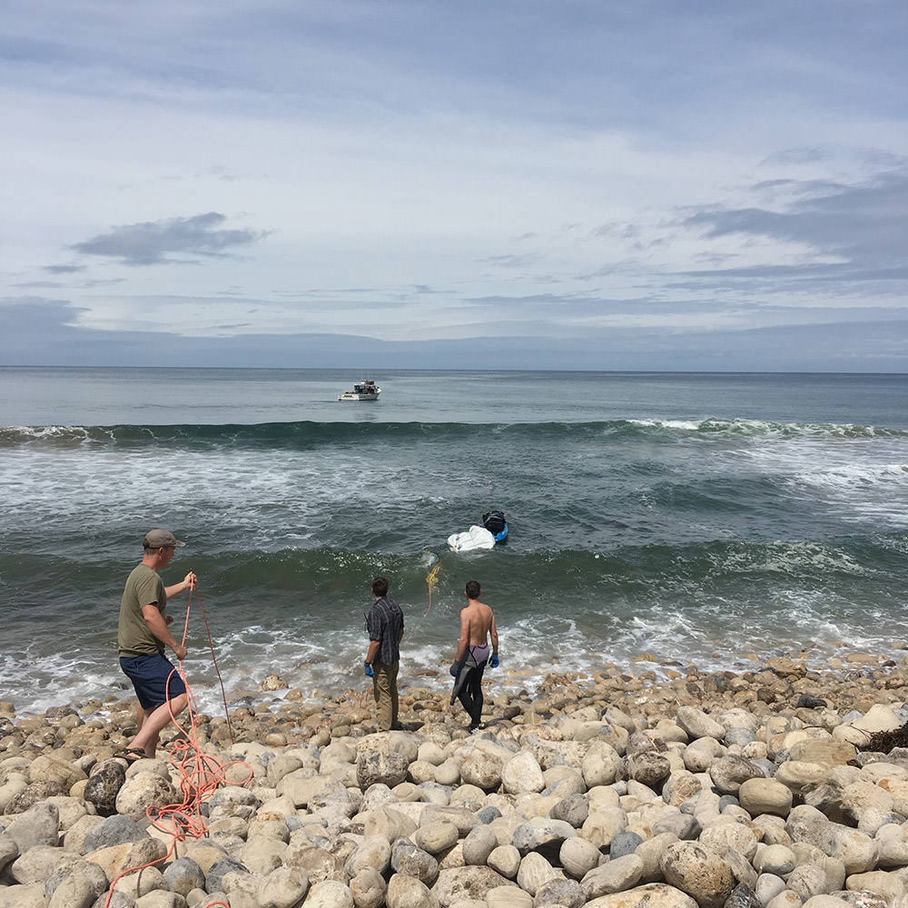 three men on a rocky beach pull in trash from the waves