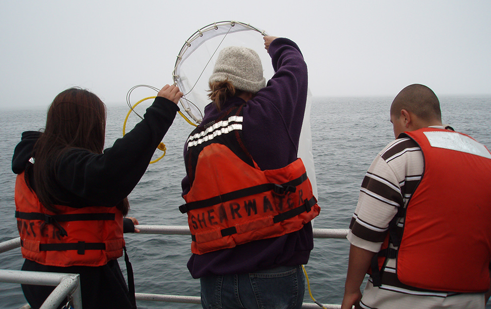 three students on a vessel face toward the ocean and pull up a net