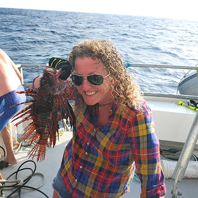 woman on a boat holding a lionfish
