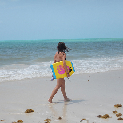 young woman on a beach with a boogie board
