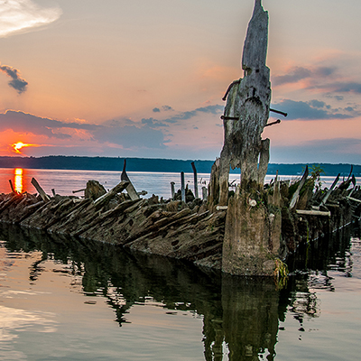 wooden shipwreck above the waterline at sunset