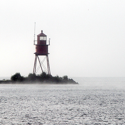 rowers pass a lighthouse in fog