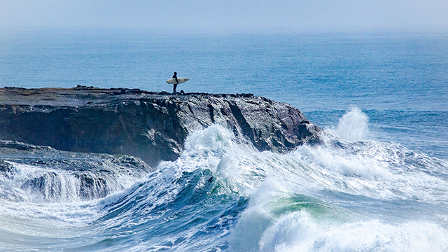 surfer standing on a cliff above waves