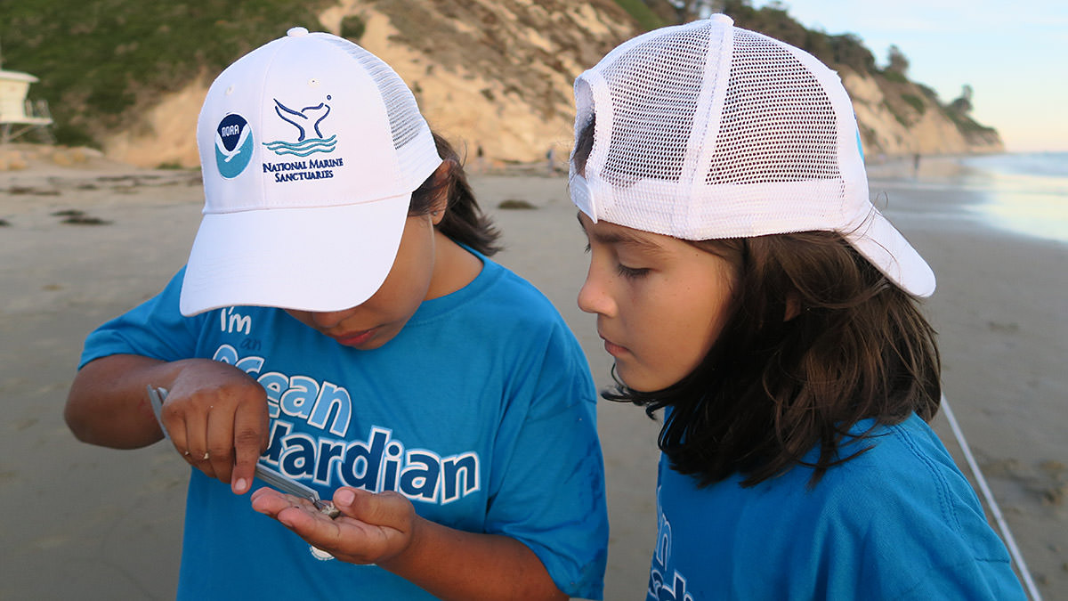 two kids examining an item they found on the beach