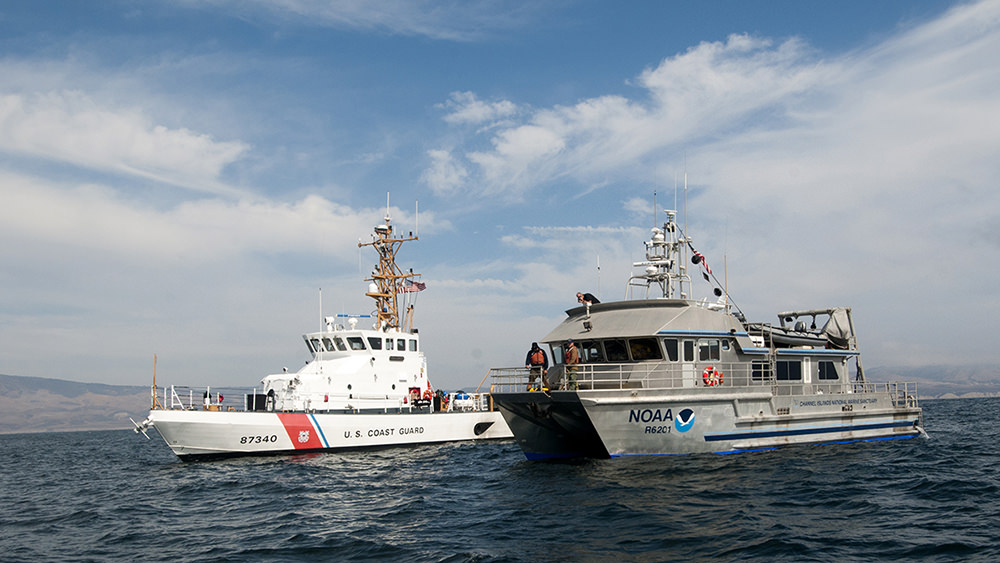 a us coast guard ship and a noaa ship at sea