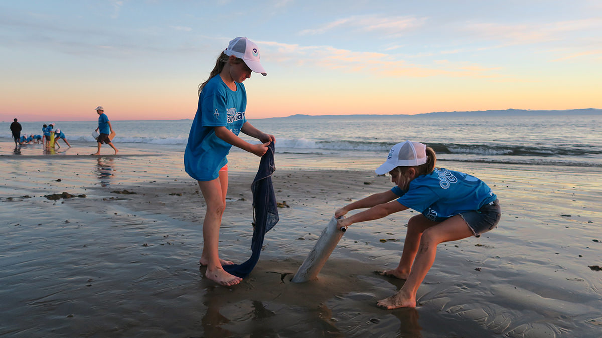 two young students monitor sand crabs