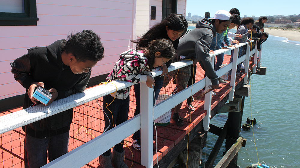 students lean over the edge of a pier to launch rovs