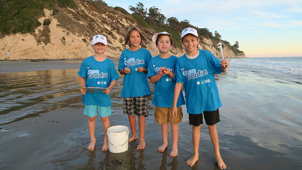 four children holding monitoring equipment and wearing ocean guardian tshirts stand on a beach