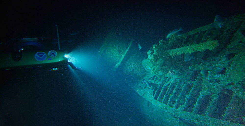 a submersible shines a light on a sunken uboat