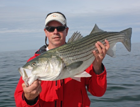 man holding a striped bass he caught