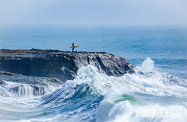 surf standing on rock cliff while waves crash around the cliff