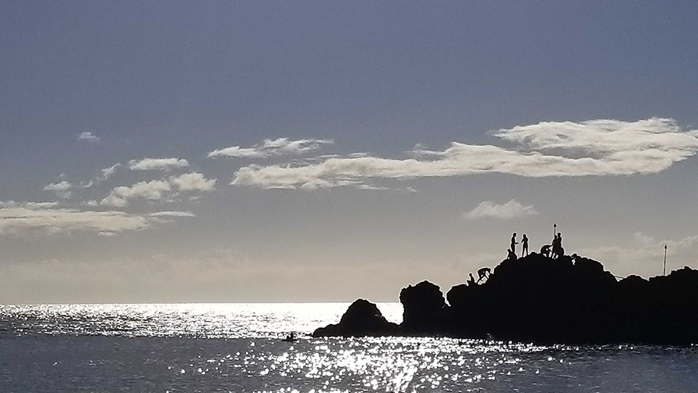 people silhouetted on a large rock in hawai'i
