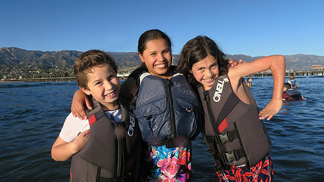 kids wearing lifevest and posing for the camera next to the water