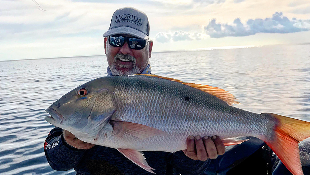 jason gabriel holds a mutton snapper