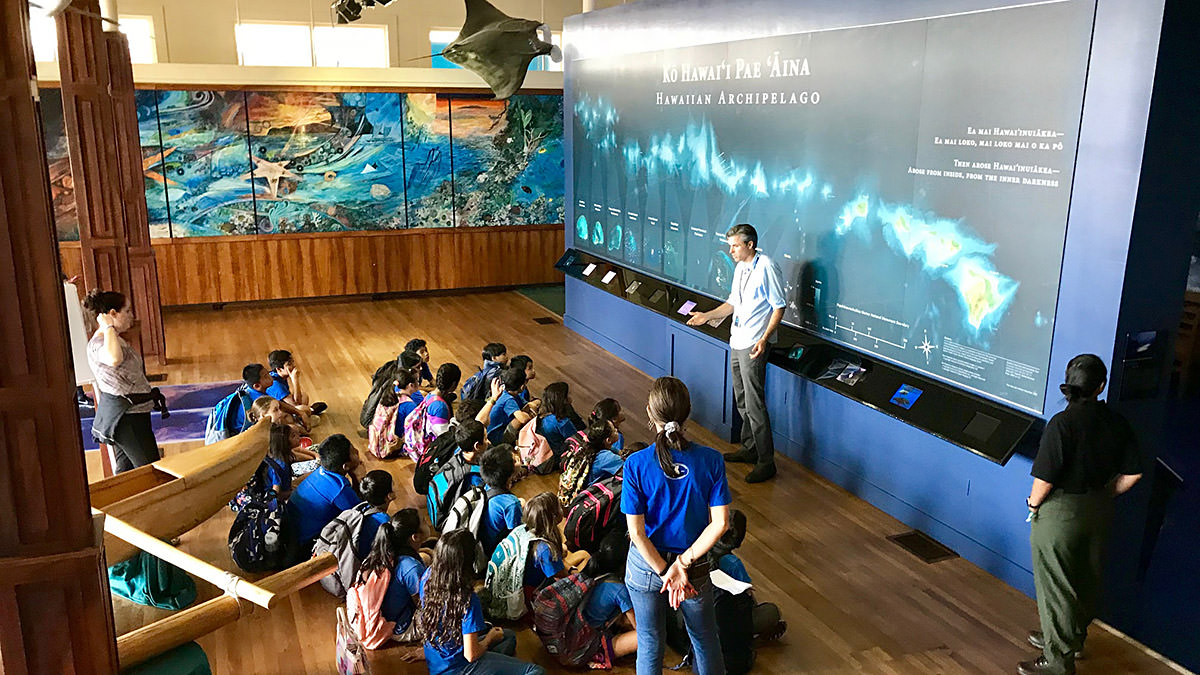 Visitors enjoy a lecture at the Mokupāpapa Discovery Center