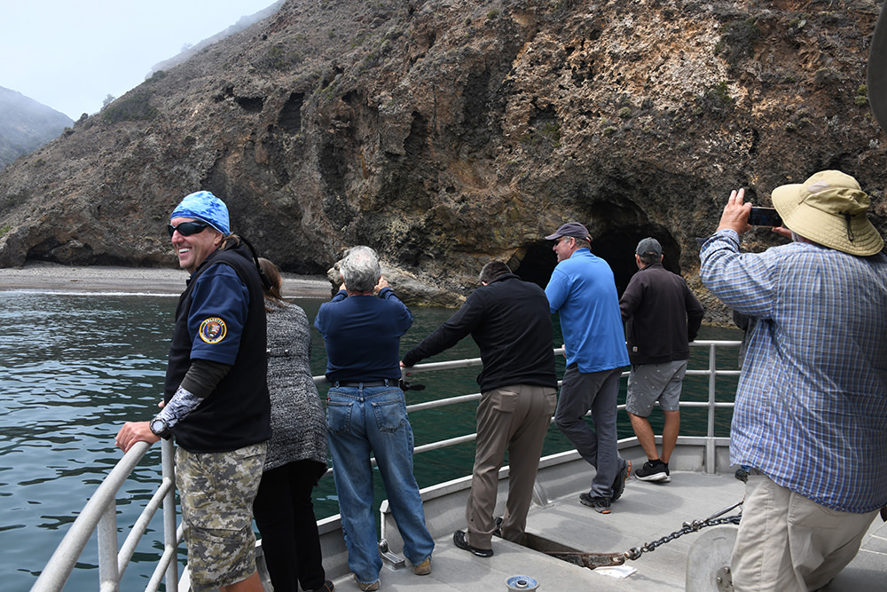 people on a boat looking at sea caves