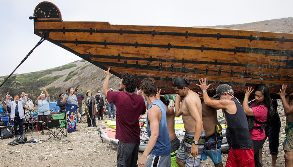 crew members carry the tomol on shore
