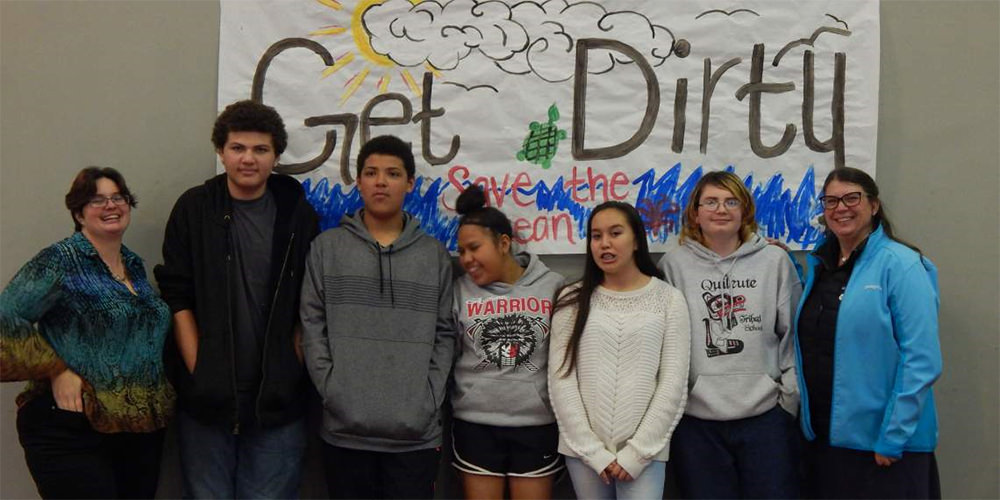 students in front of a sign that says get dirty