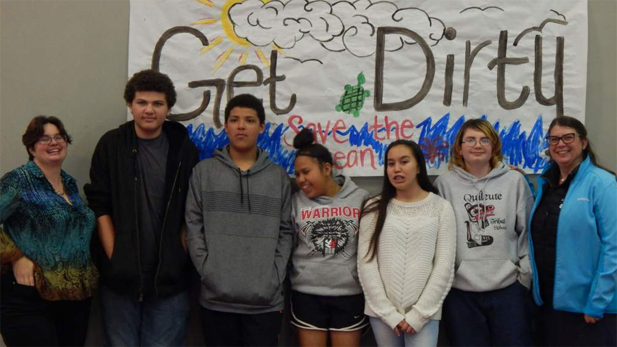 students standing in front of a sign that says get dirty