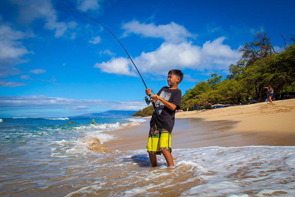 boy standing in waves fishing