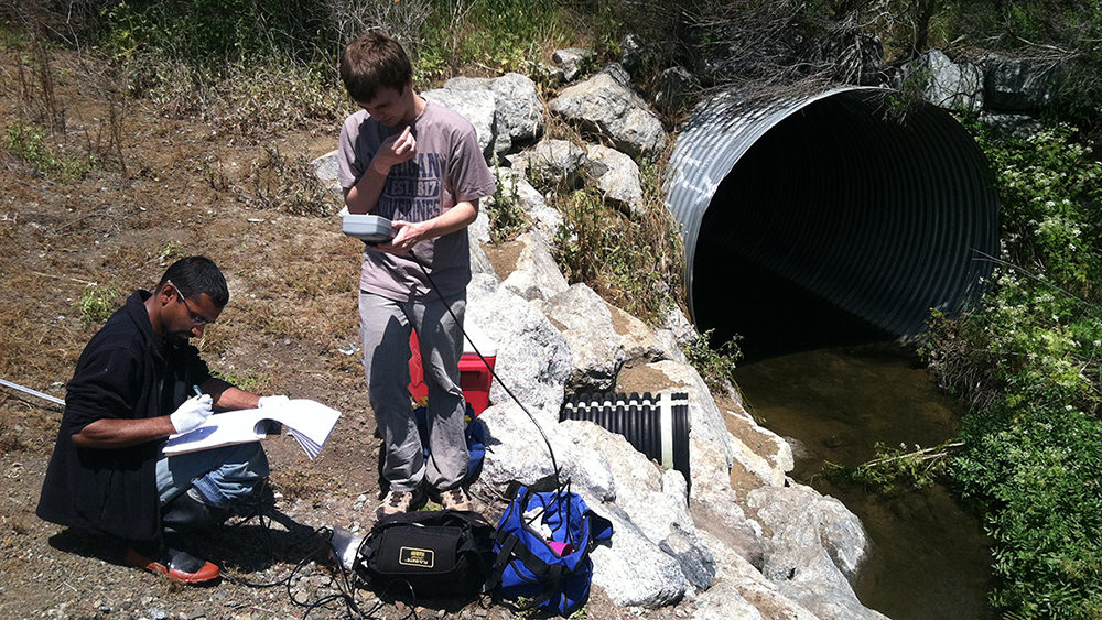 two people with monitoring equipment standing next to a culvert