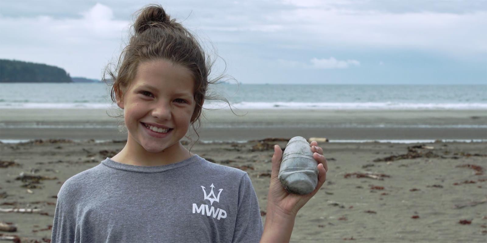 girl holding up marine debris