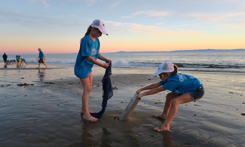 Two children cleaning up a beach
