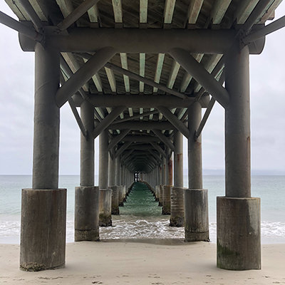 view of the underside of a pier stretching into the ocean