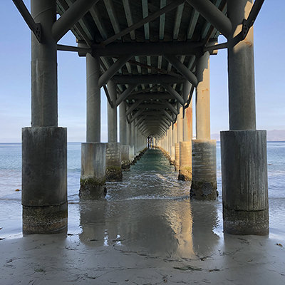 underside of a pier stretching into the ocean