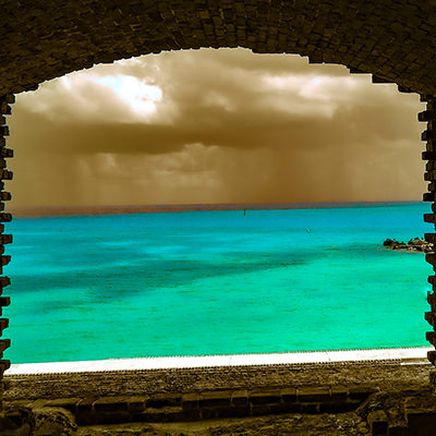 the ocean through an opening in a brick wall