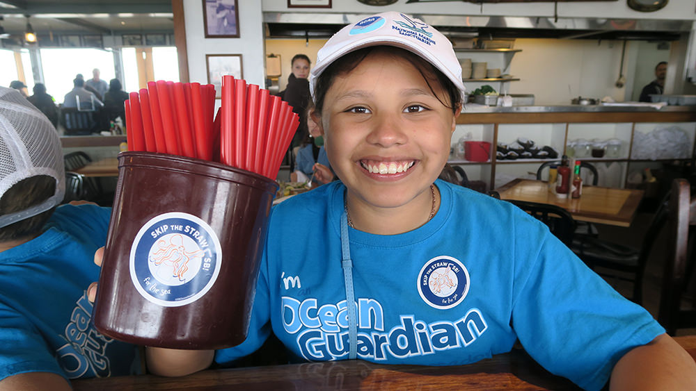 "A young student holds up a container filled with red, plastic straws. She had placed a sticker on the side of the container that says ""Skip the Straw""."