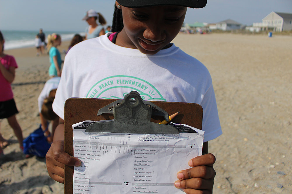 a student holding a data collection worksheet