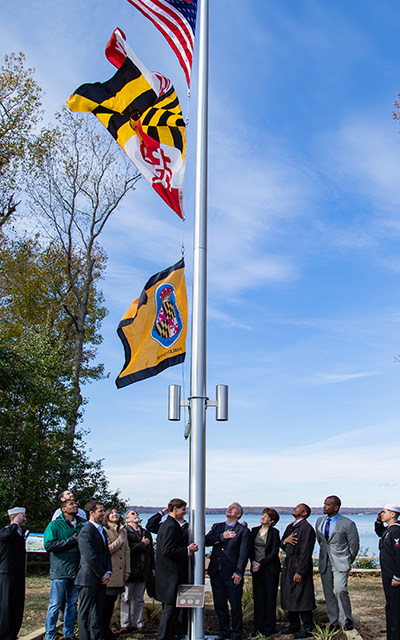 people raising the u.s., maryland, and charles county flags