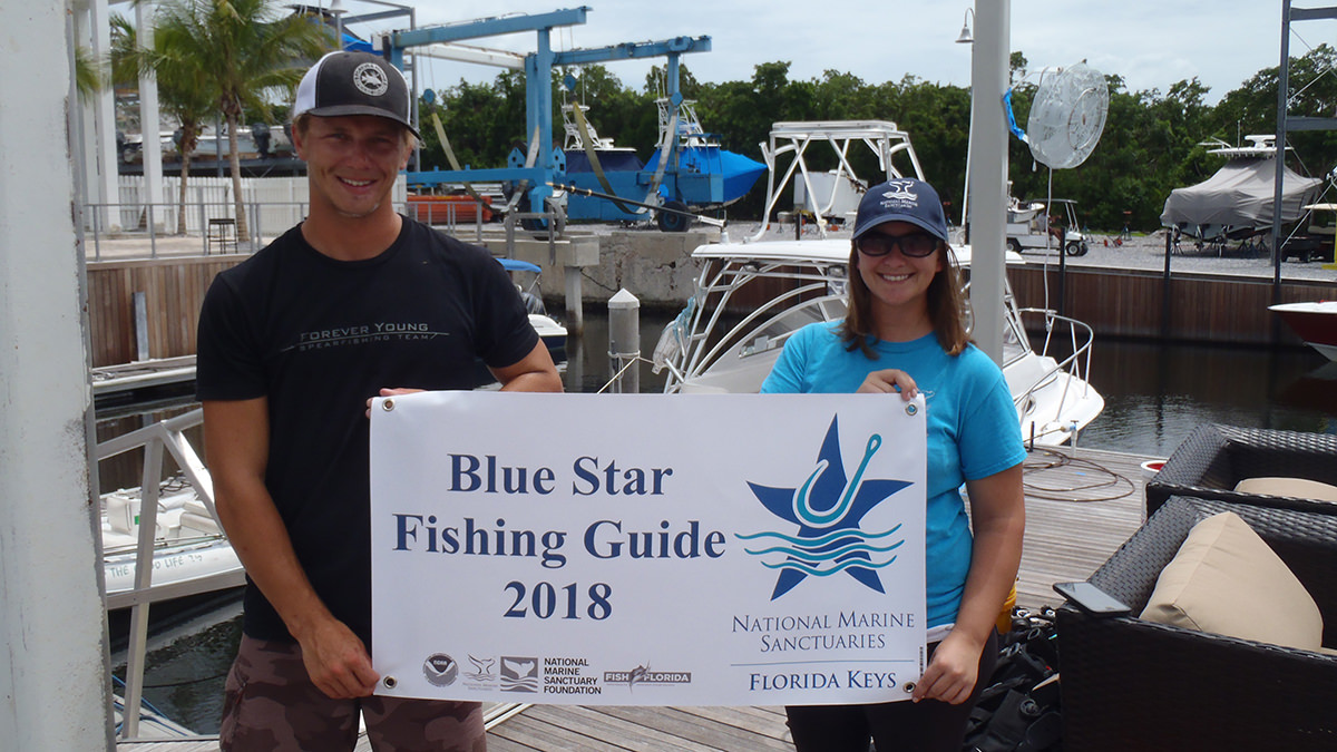 man and woman holding blue star fishing guide sign