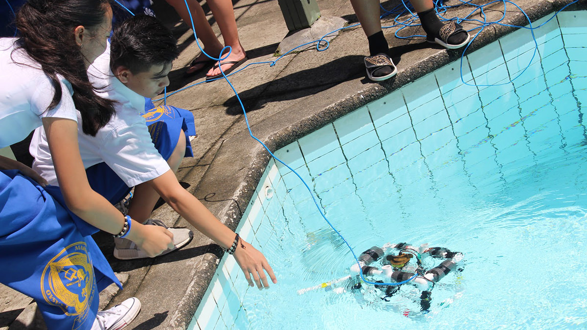 students launching a remotely operated vehicle in a pool