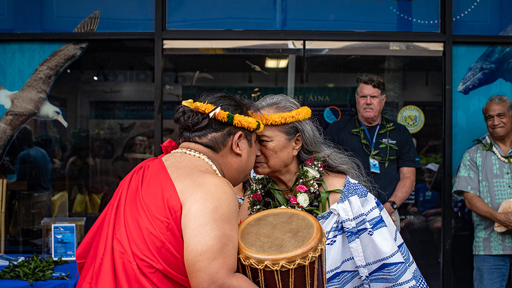 two people touching noses in the traditional hawaiian greeting
