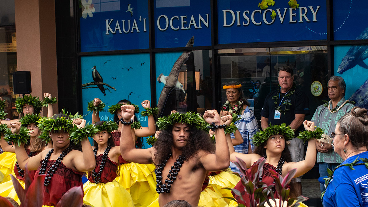 people performing a hula in front of kaua'i ocean discovery