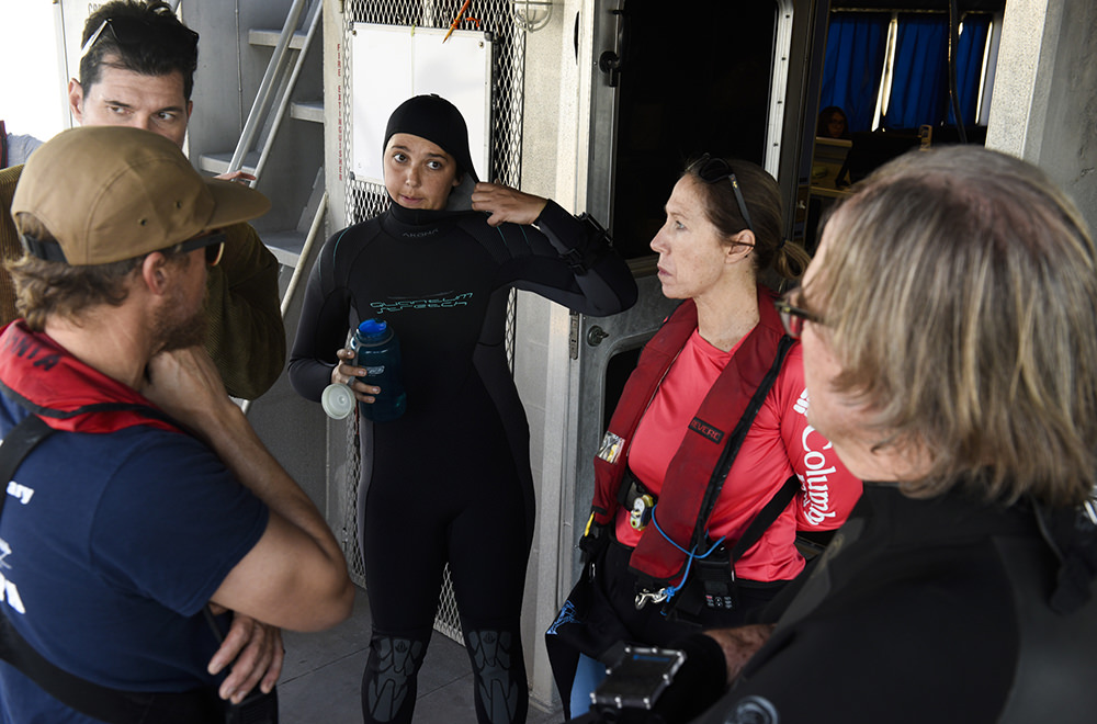 people in wetsuits and lifejackets standing on the ship's deck