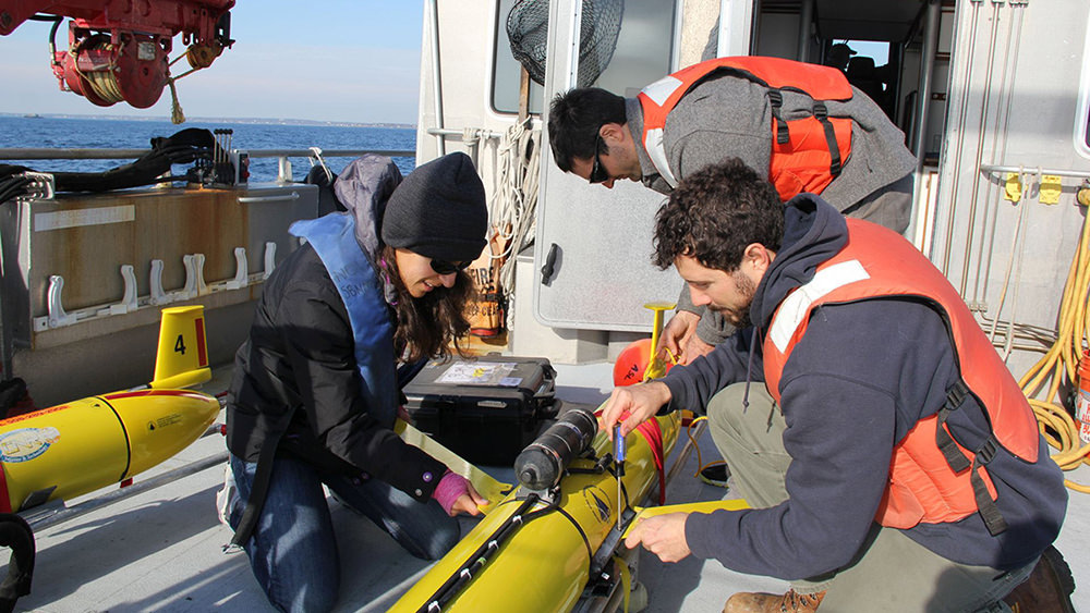 three people gathered around a yellow autonomous underwater vehicle on the deck of a ship