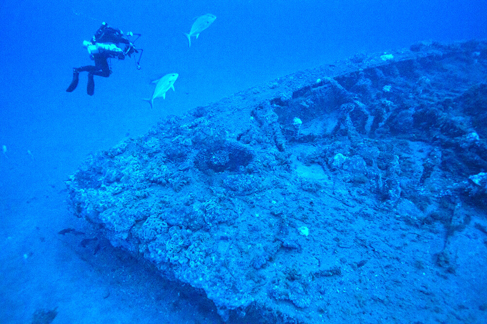 A diver inspects the wreck of the monitor