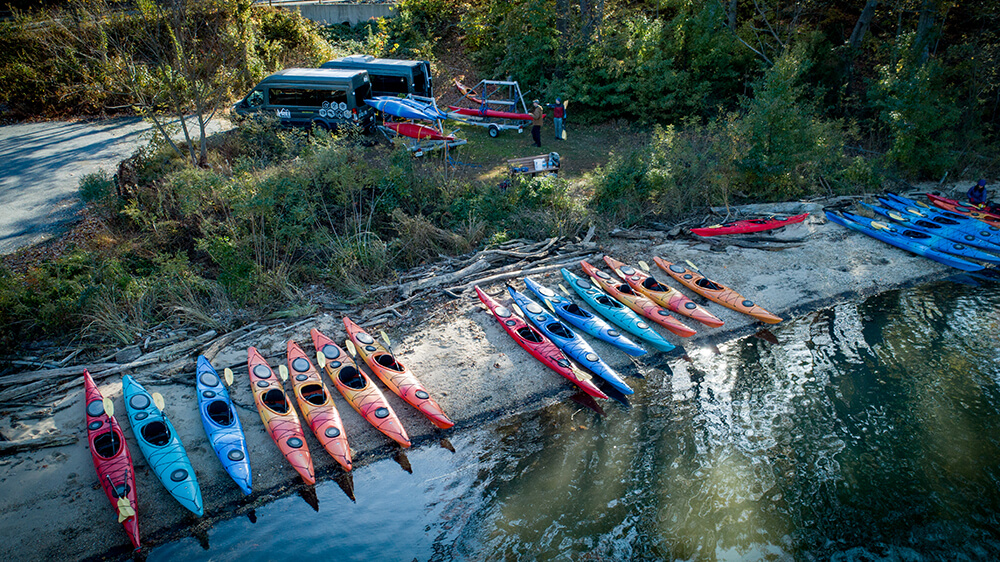 kayaks lined up along a river bank