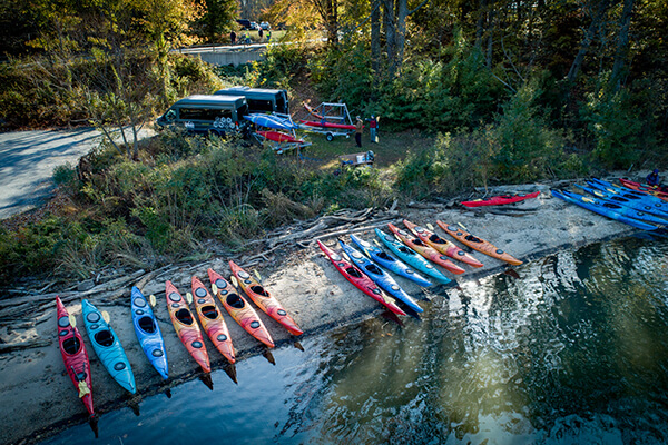 kayaks lined up on a river bank