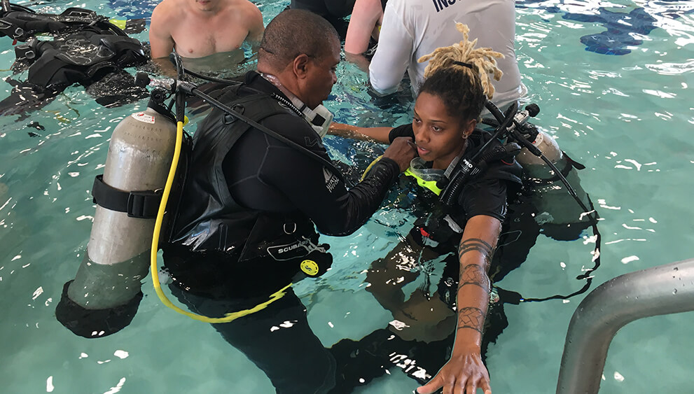 Scuba instructors teaching students in a pool